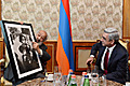 At the meeting with President Serzh Sargsyan the world-famous photographer Ara Güler presents him with one of his works